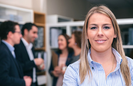 Portrait of blonde woman looking at camera in office