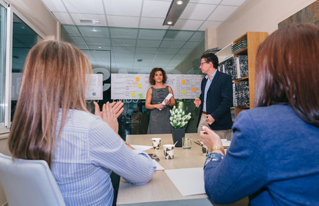 Teamwork applauding to woman chief for success in business project