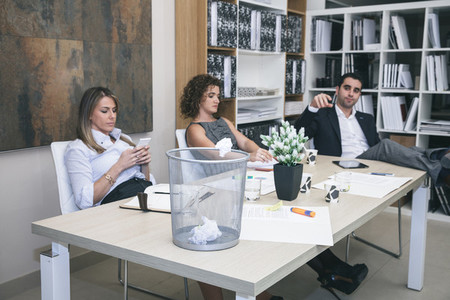 Colleagues boring in office and businessman throwing paper on basket
