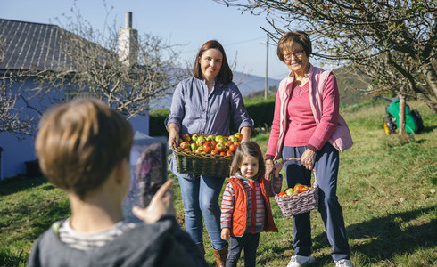 Family with apples in basket posing to photo