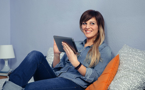 Happy beautiful woman using tablet in a bed