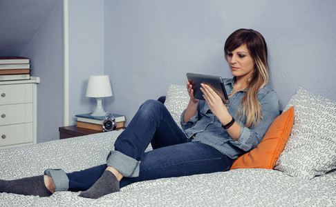 Young beautiful woman looking tablet in a bed
