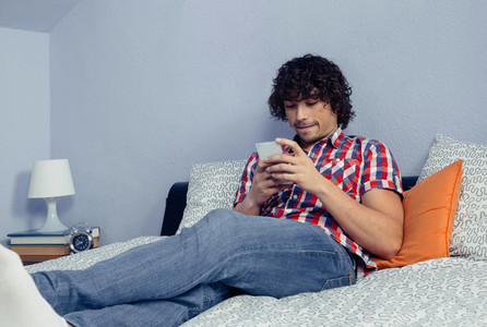 Young handsome man looking smartphone in a bed