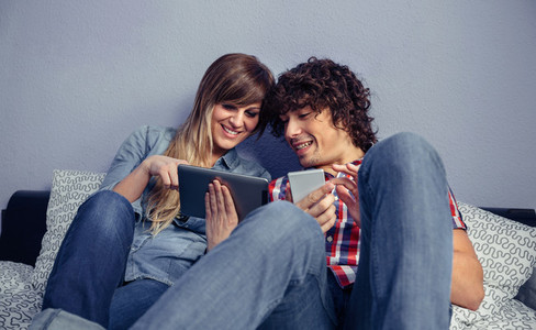 Couple in love looking electronic tablet and laughing