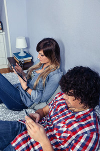 Couple in love using electronic devices on bed