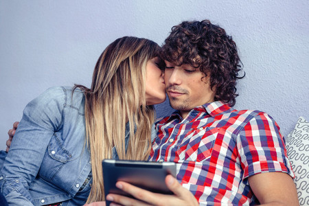 Beautiful young woman kissing to man looking tablet