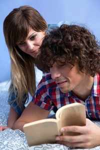 Couple reading a book on the bed
