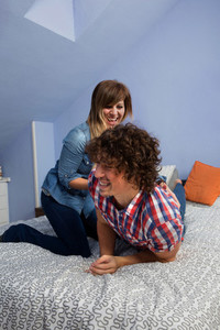 Young woman tickling husband