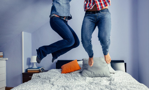 Unrecognizable couple jumping on the bed