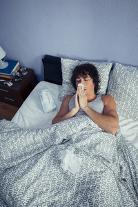 Sick man sneezing and covering nose with tissue