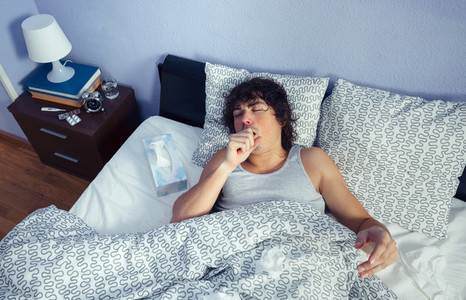 Portrait of sick man coughing lying on bed
