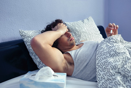 Sick man looking temperature in thermometer on bed