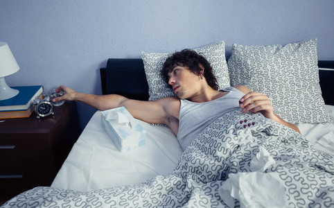 Young sick man taking medicines lying on bed