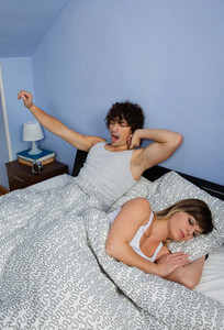 Man waking up while his wife sleeps