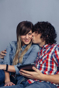 Man kissing to young woman and holding tablet