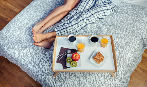 Healthy breakfast on tray and couple legs over bed