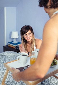 Happy woman in bed looking to breakfast served by man