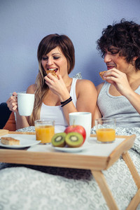 Couple having breakfast in bed served over tray