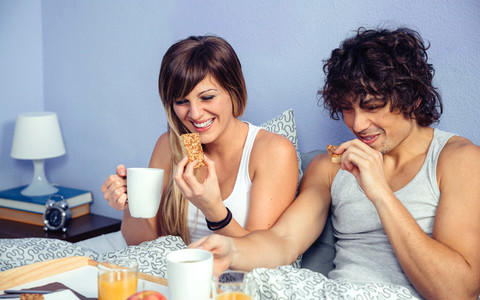 Couple laughing and having breakfast in bed at home