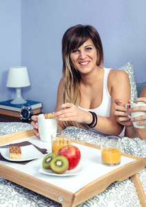 Beautiful young woman laughing and having breakfast in bed
