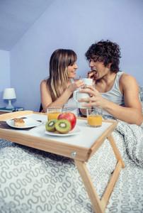 Young woman feeding happy man in bed breakfast