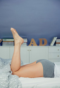 Closeup of beautiful woman legs lying on bed