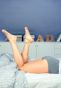 Close up of beautiful woman legs lying on bed