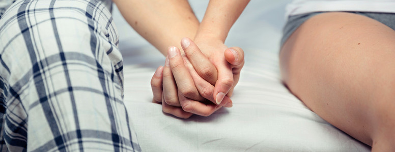 Young couple holding hands sitting over a bed