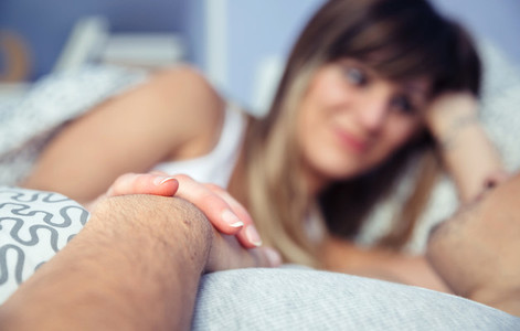 Couple in love holding hands lying on bed