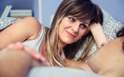 Beautiful woman looking to man lying on bed