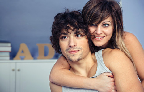Couple in love embracing and smiling on bedroom
