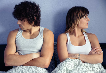 Angry couple sitting on bed with crossed hands