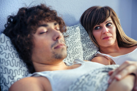 Angry woman looking to young man sleeping