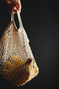 Hand holds an eco net bag with banana branch against black background