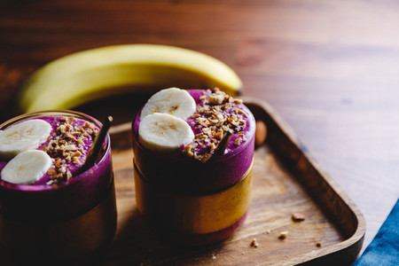 Two glasses with violet berry and banana smoothie are served crushed almond on a wooden tray
