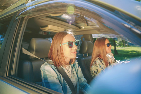 Two happy young women traveling in car