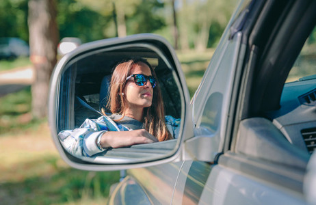 Reflection in side view mirror of woman driving car