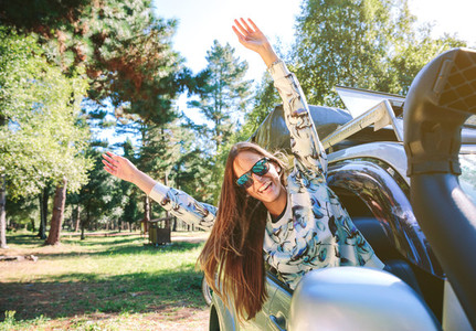 Happy woman raising arms through the window car