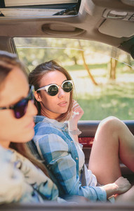 Two young women resting sitting inside of car