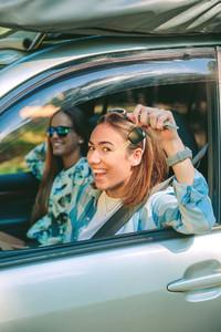 Happy woman showing car keys ready to start travel
