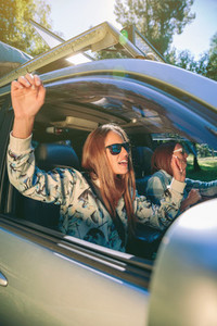 Happy woman raising arms and having fun inside of car