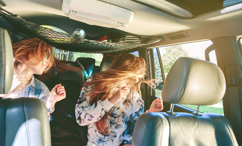 Happy women dancing and having fun inside of car
