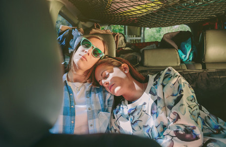Tired women friends sleeping in a rear seat car