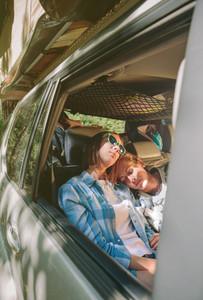 Tired women friends sleeping inside of car