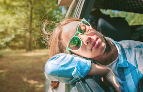 Young woman with her head over the door car
