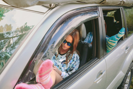 Women resting with her legs over open window car