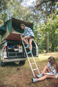 Woman descending ladder form tent over car