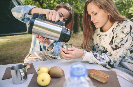 Woman pouring coffee in cup to friend