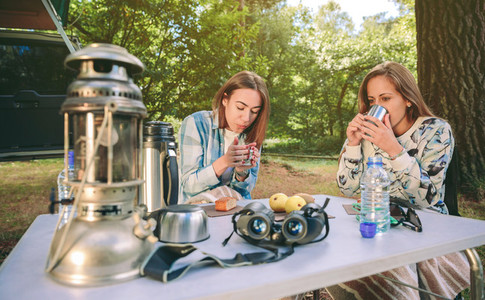 Women drinking cups of coffee in forest