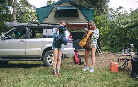 Young women opening sleeping bags in campsite